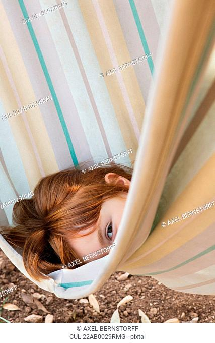 Young girl looking out from a hammock