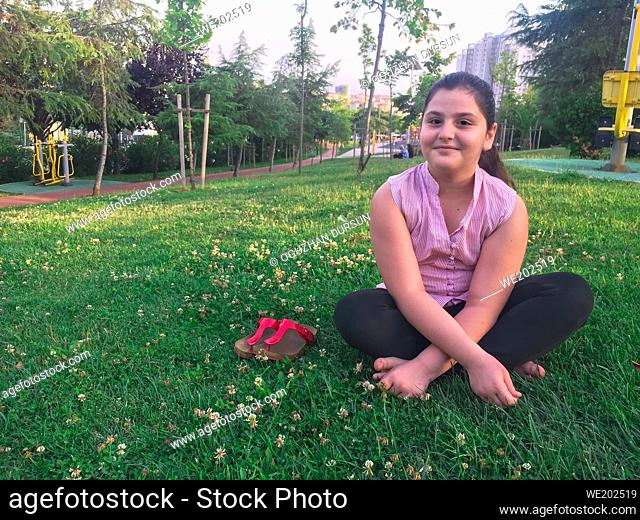 young teenager girl sitting on green grass in Summer and smiles to the camera
