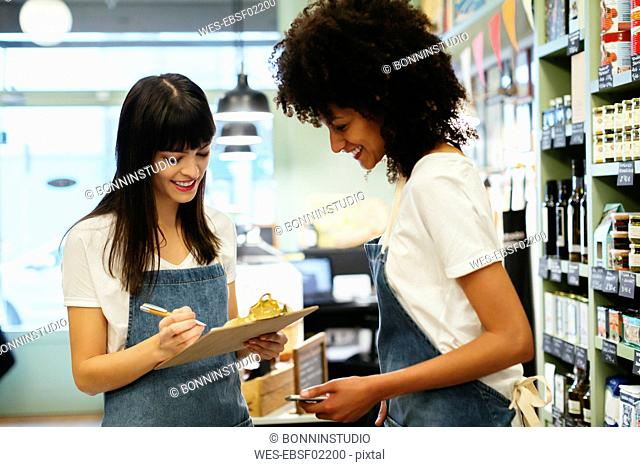 Two smiling women in a store with clipboard