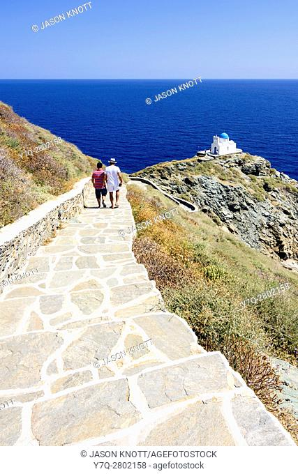 Tourists walking down the steps to the whitewashed blue domed Church of the Seven Martyrs, Sifnos Island, Cyclades, Greece