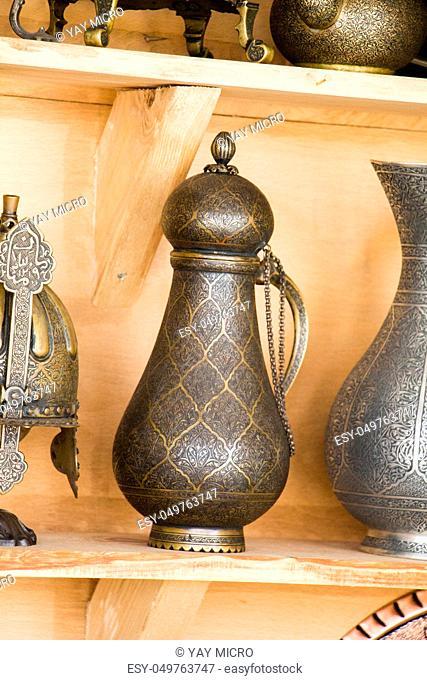 Ancient metal jug in oriental style in antique market