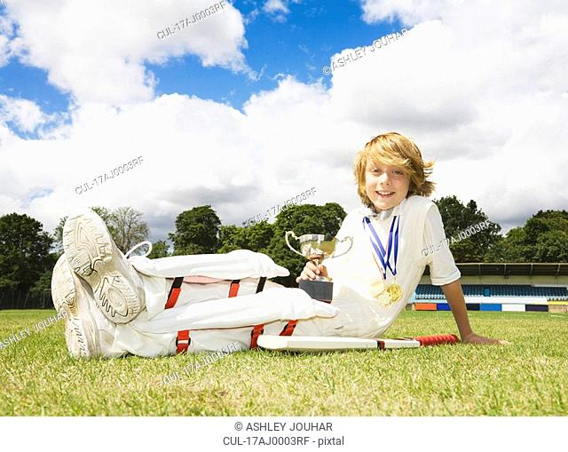 Boy Cricketer with medals and Trophy