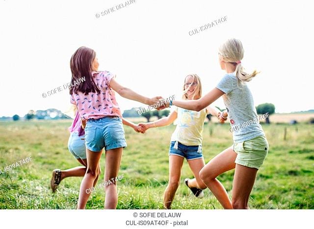 Girls dancing in ring on field, Flanders, Belgium
