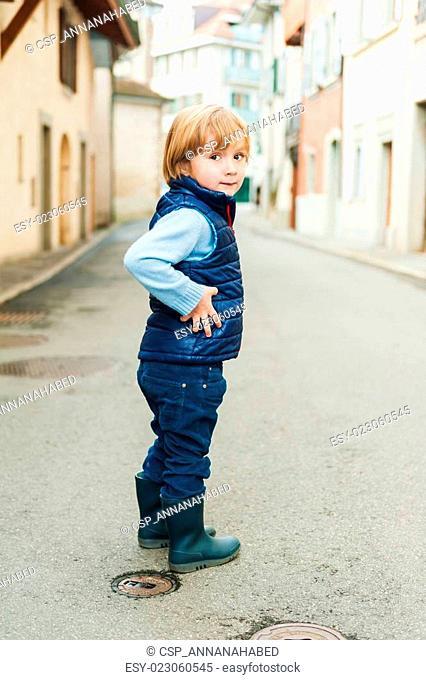 Outdoor portrait of a cute little boy, wearing blue waistcoat and rain boots