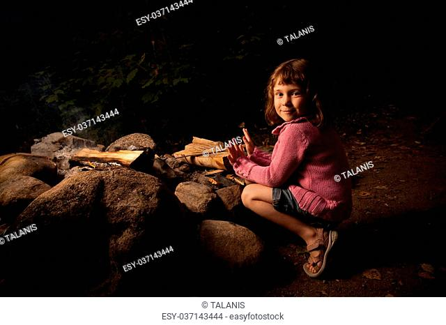 Little girl getting warm near a campfire at night
