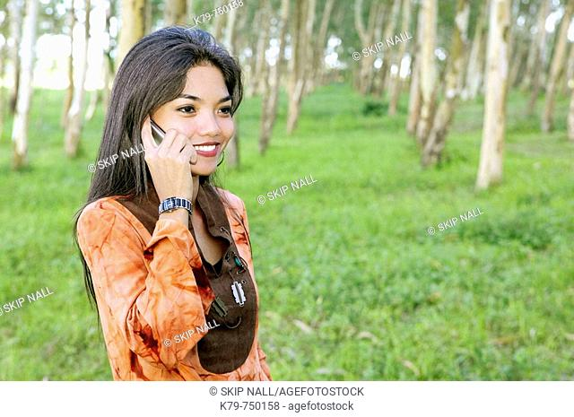 Philippine woman using cell phone in the park surrounded by trees