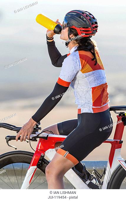Female cyclist taking drink from water bottle on race bicycle on sunny open road