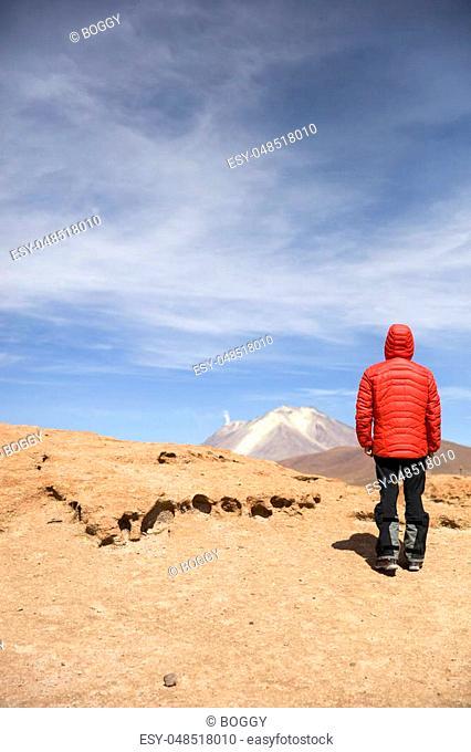 Young man looking at View at Licancabur volcano in Reserva Nacional de Fauna Andina Eduardo Avaroa in Bolivia