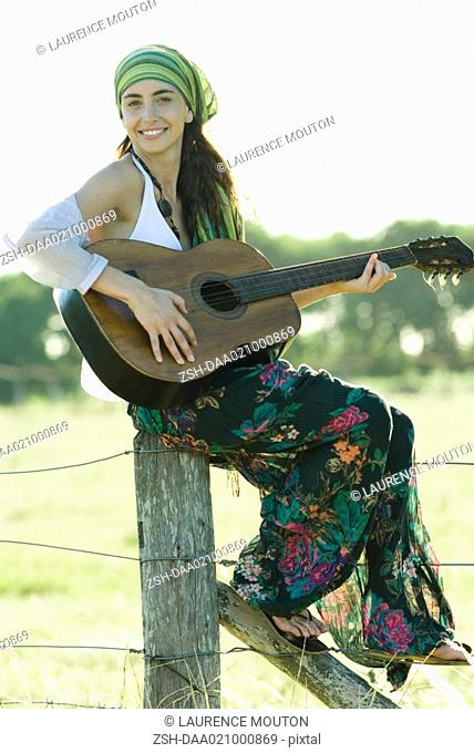 Young hippie woman sitting on fence post, playing guitar