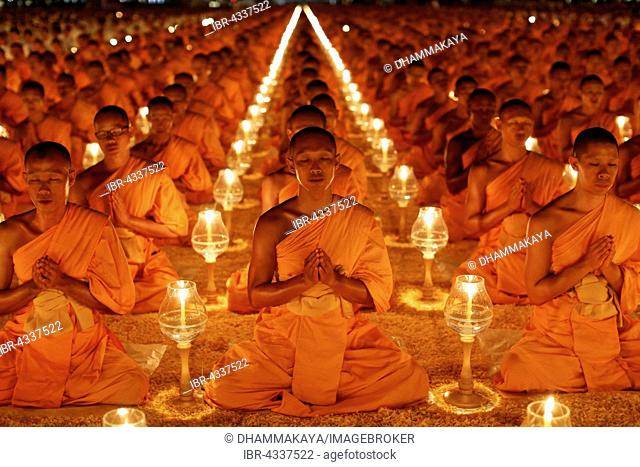 Monks sitting in rows praying and meditating by candlelight, Wat Phra Dhammakaya Temple, Khlong Luang District, Pathum Thani, Bangkok, Thailand