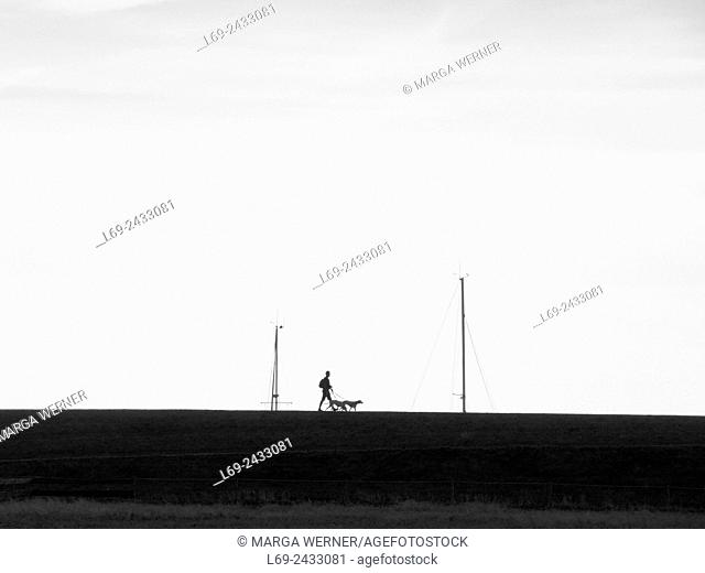People and dog walking on a dyke of island Neuwerk, Elbe estuary, North Sea, Hamburg, Germany