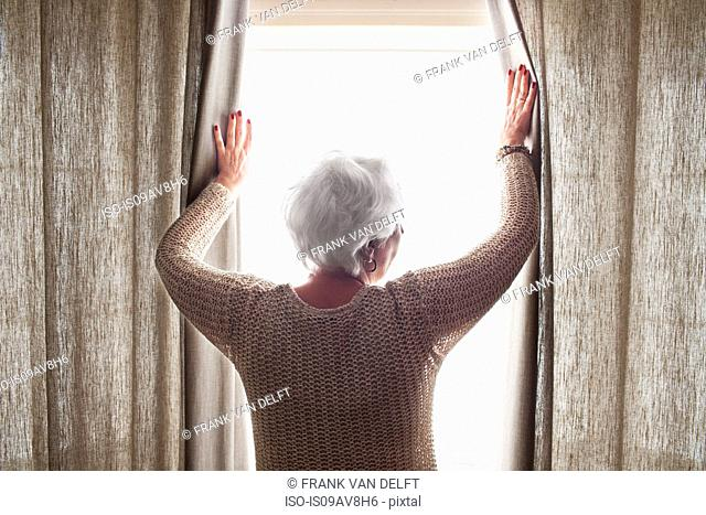 Senior woman, opening curtains, rear view
