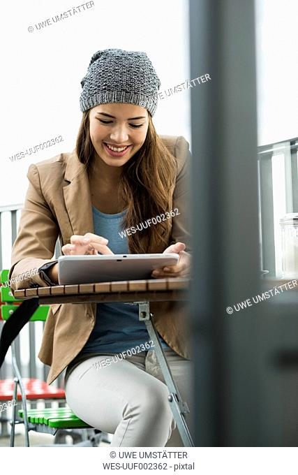 Young woman sitting at sidewalk cafe using digital tablet