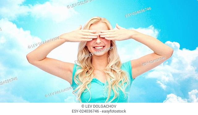 emotions, expressions and people concept - smiling young woman or teenage girl covering her eyes with palms over blue sky and clouds background