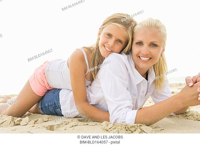 Caucasian mother and daughter laying on beach