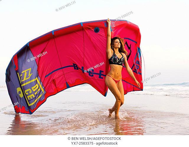 Woman with a kitesurf at the beach. Tarifa, Costa de la Luz, Cadiz, Andalusia, Southern Spain