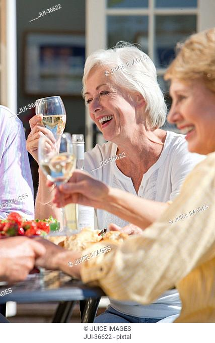 Smiling senior women drinking wine and enjoying lunch on sunny patio