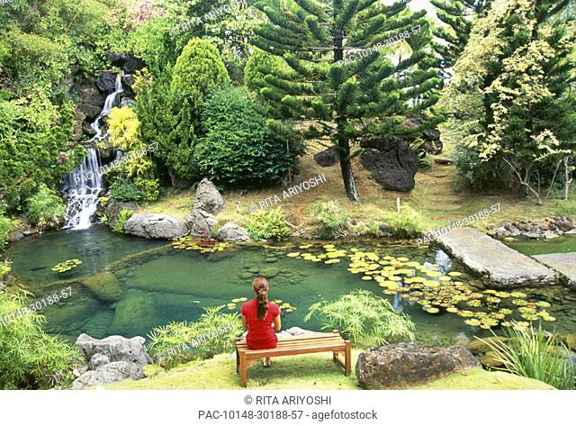 Hawaii, Kauai, Kilauea, Na Aina Kai Botanical Garden, scenery peaceful waterfall and pond, woman sitting on bench