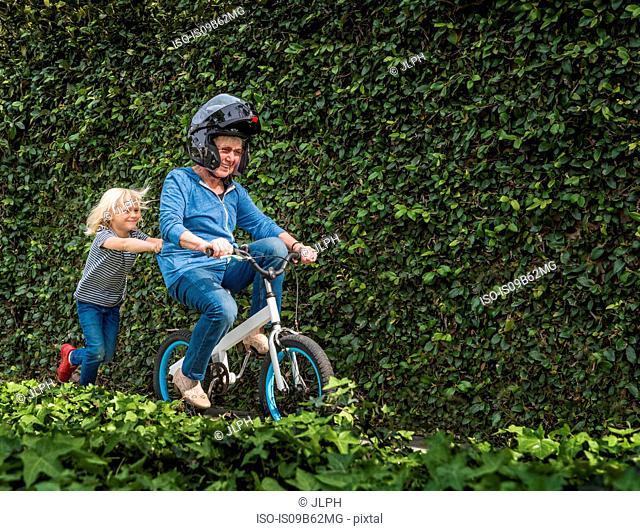 Grandson pushing grandmother on his bicycle