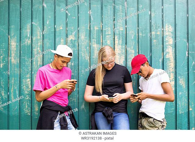 Teenage girl and teenage boys (14-15) using smart phones
