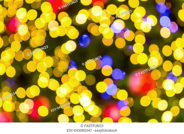 Golden Bokeh of Christmas balls and Christmas tree with light background