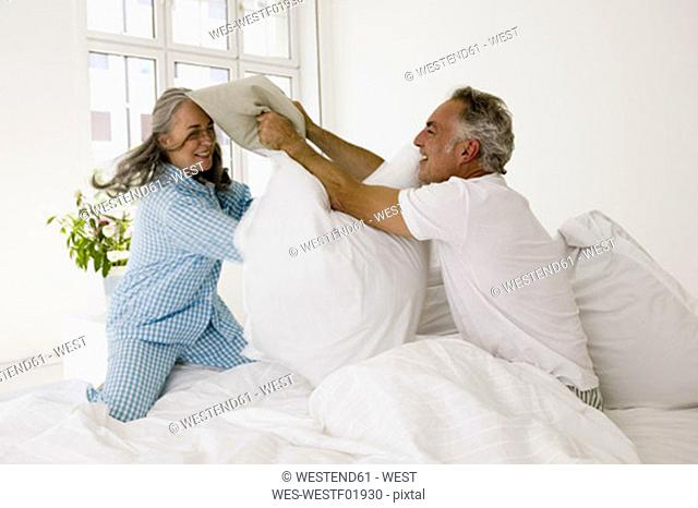 Mature couple having pillow fight on bed