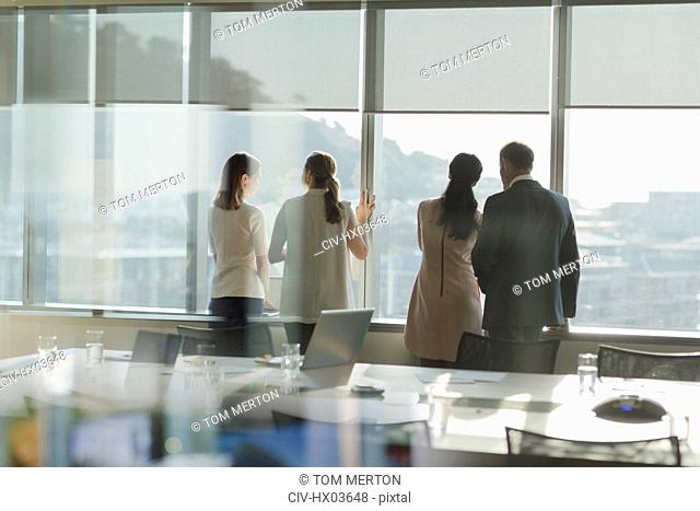 Business people looking out sunny window in urban conference room