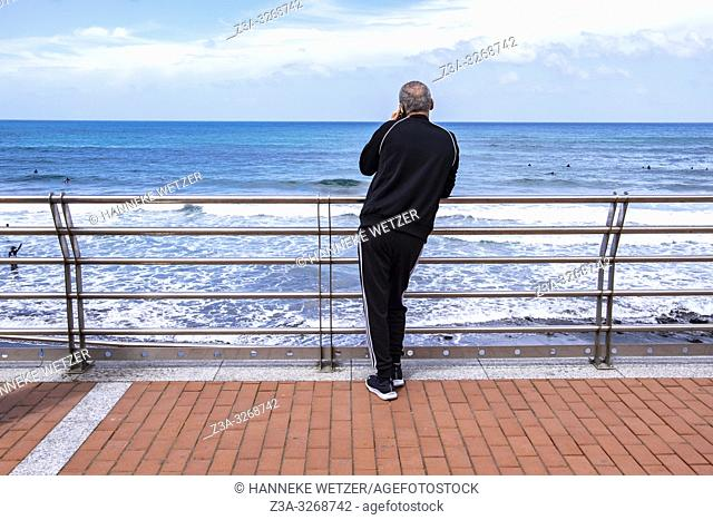 Man making a phonecall at the coast of Las Palmas de Gran Canaria