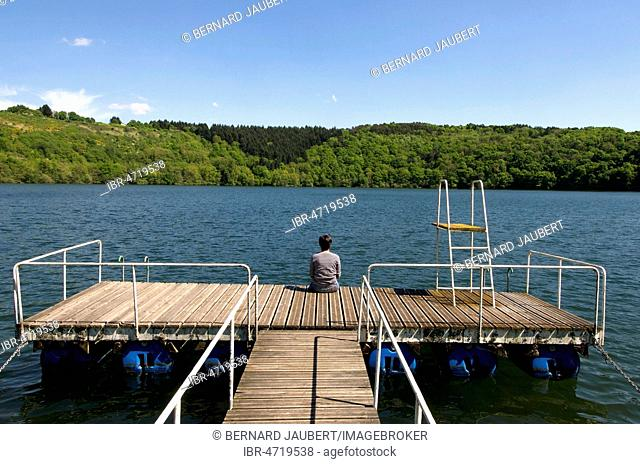 Adult woman back sitting on a pontoon at the edge of a lake surrounded by rows of trees, Puy de Dome department, Auvergne, France