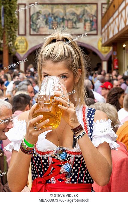 Germany, Bavaria, Munich, Oktoberfest, Young Woman Drinking Beer