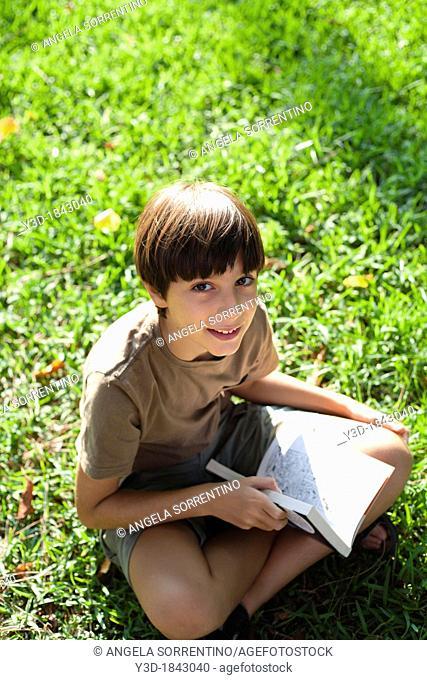 Boy reading a book outdoor in a park