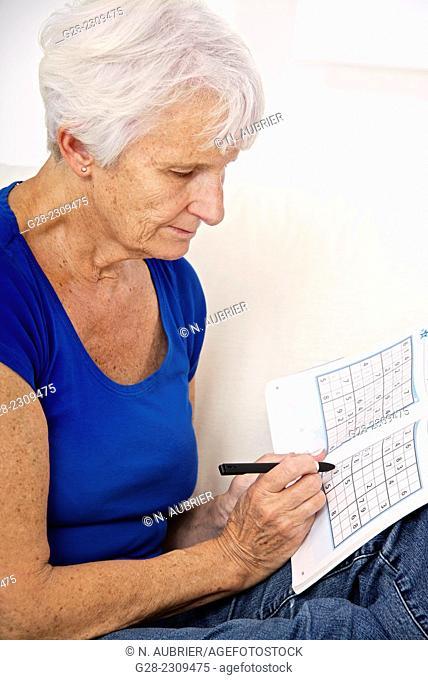 Senior woman doing Sudoku, for alzheimer