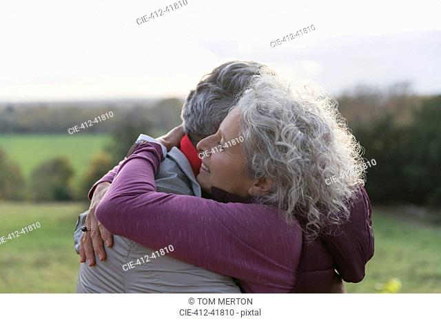 Affectionate senior couple hugging in field