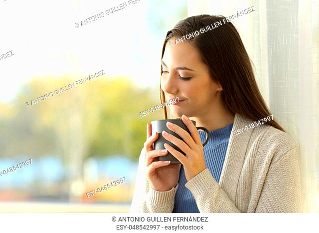 Portrait of a pensive relaxed woman drinking coffee near a window in a house interior