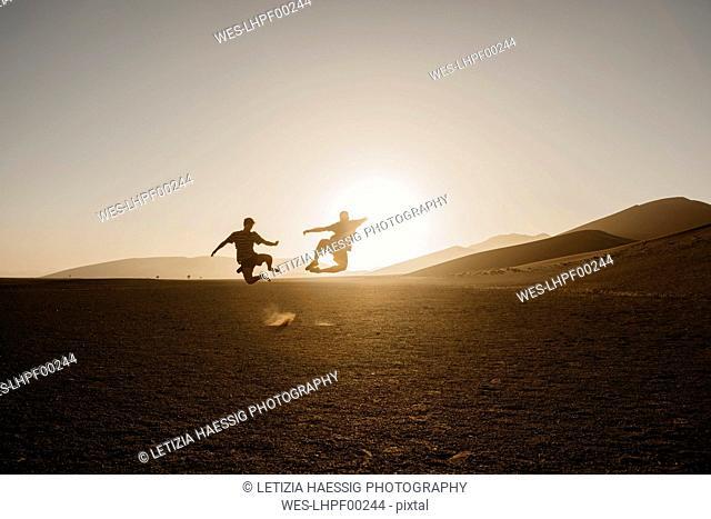 Namibia, Namib desert, Namib-Naukluft National Park, Sossusvlei, two men jumping at Dune 45 at sunrise