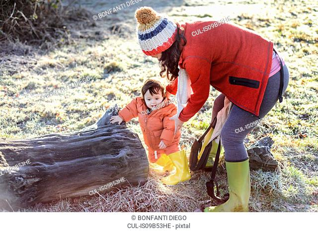 Mother steadying baby boy, outdoors, in winter