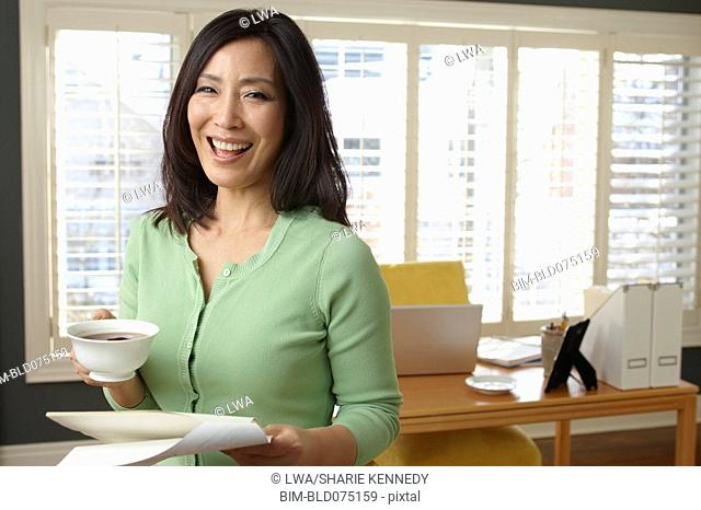 Korean woman drinking coffee and holding paperwork in office