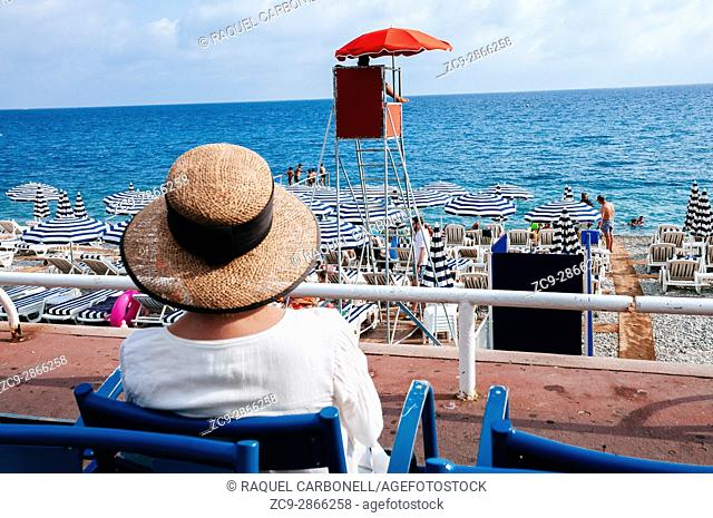 Woman with hat sitting on chair while loocking over 'Neptune Page' stone beach. Nice, French Riviera, France