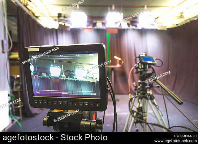 Film camera on a tripod in a television broadcasting studio, spotlights and equipment