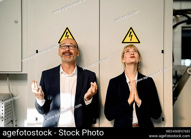 Businessman and businesswoman under high voltage warning sign in a factory