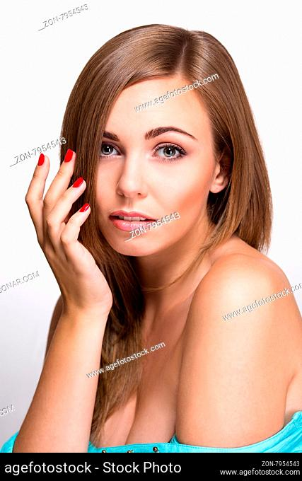 Close-up portrait of beautiful woman isolated on white background. Blond woman with red nails looking at the camera