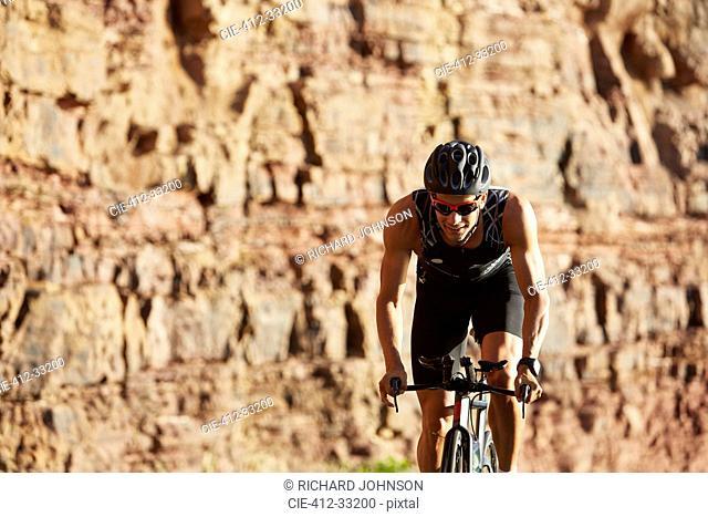 Male triathlete cyclist cycling along sunny rocks