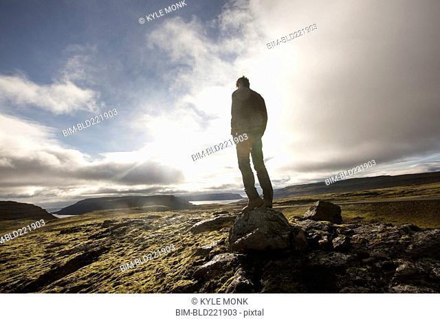 Caucasian man standing on rock in field