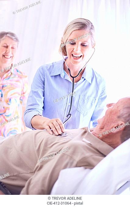 Doctor using stethoscope on senior man