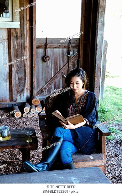 Chinese woman reading in barn
