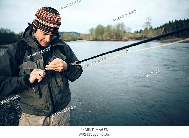 Middle aged man fly fishing on the Hoh River, Olympic National Park, Washington