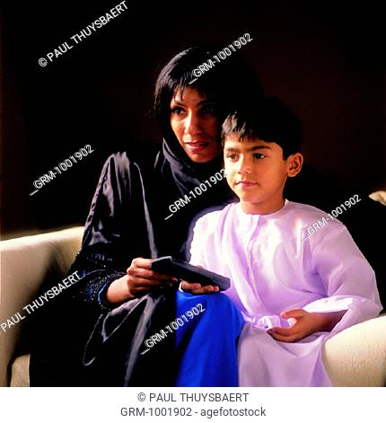 Arab mother and young boy watching TV