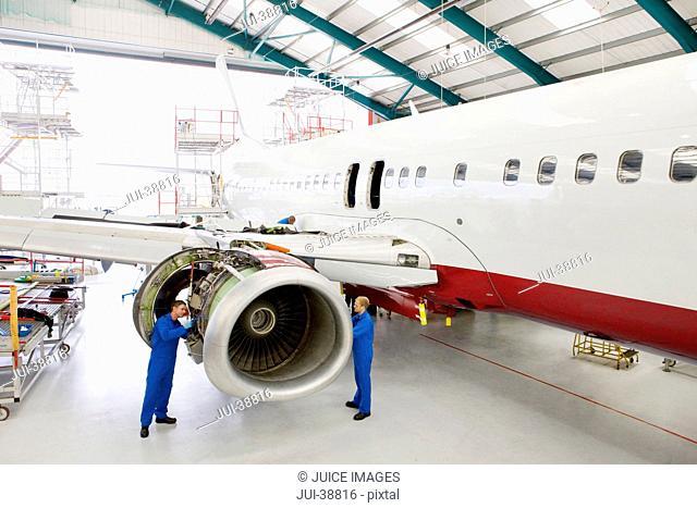 Engineers assembling engine on passenger jet in hangar