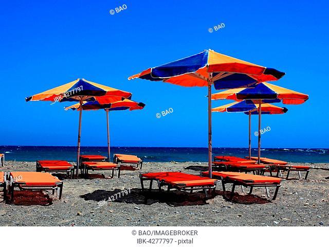 Colourful beach chairs and umbrellas on beach, blue sea, Crete, Greece
