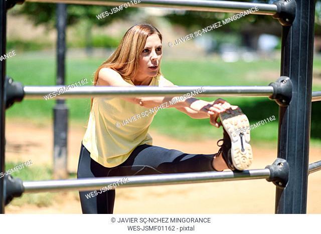 Woman exercising at a bar in a park